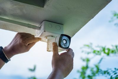 Man installing home security camera (How to Use a Home Security Camera, and How it Could Replace a Video Doorbell)